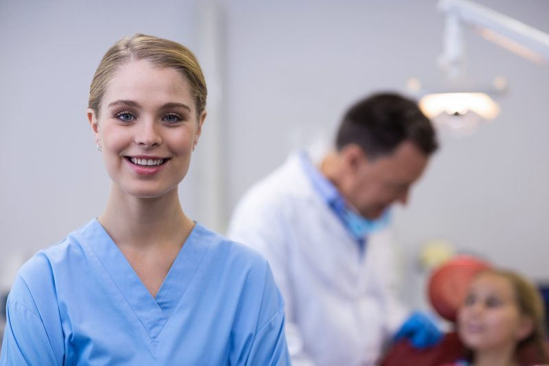 Dental Assistant standing and smiling next to family dentist